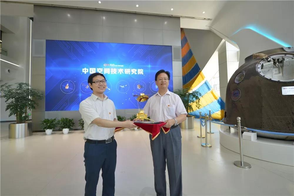 党委书记张士军代表中国国家画院在中国空间技术研究院接受中国航天科技集团专家齐国生赠予的航天器模型