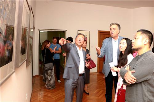 中国国家画院国画院副院长于文江向黑山名誉总统武亚诺维奇介绍展览作品