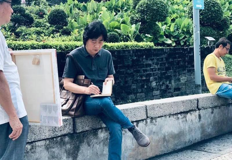福建师范大学美术学院副院长卢志强拿着小本随时写写画画