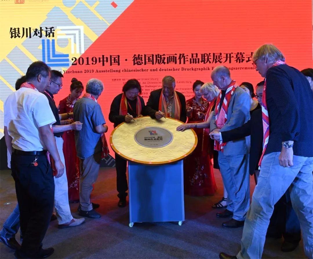 嘉宾用手印和签名开启画展的启动仪式